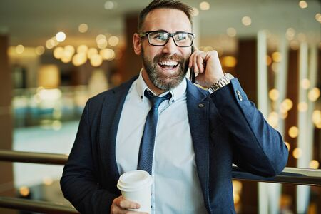 happy work: Happy businessman with plastic glass speaking on the phone Stock Photo
