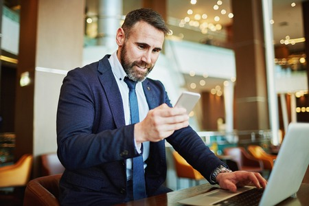 technology career: Contemporary business agent reading sms while sitting in front of laptop Stock Photo