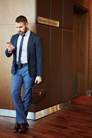 business briefcase: Contemporary employee with briefcase reading sms on the corner of lounge