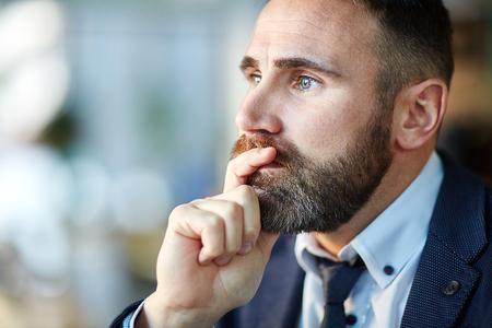 Hombre pensativo tocar su barbilla