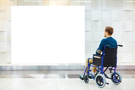 paraplegico: chico Deshabilitar en silla de ruedas mirando el cartel en blanco en la pared