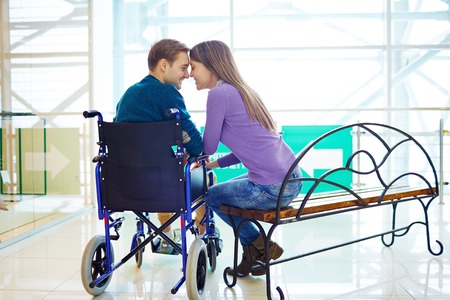 Amorous girl sitting on bench close to her boyfriend in wheelchair