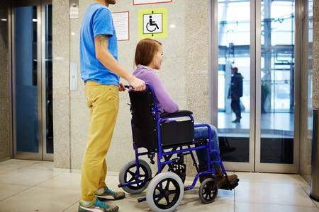 paraplegic: Guy y su novia en silla de ruedas esperando para el elevador Foto de archivo