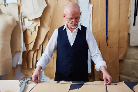 craftsmen: Mature tailor working with patterns and measuring tape