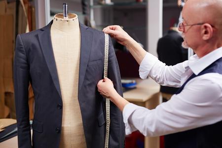 Ältere Schneider Maßnahmen zu ergreifen, der Mann Jacke auf Mannequin