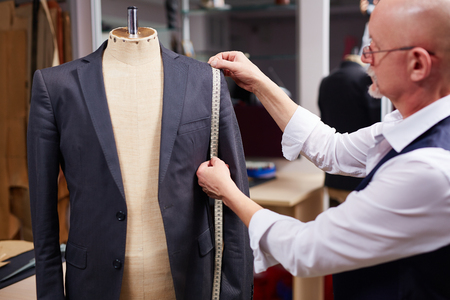 Mature tailor taking measures of man jacket on mannequin