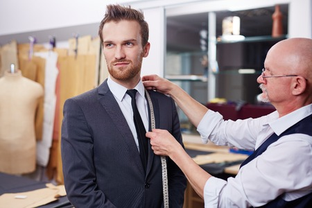 tailor measure: Young modern businessman visiting tailor
