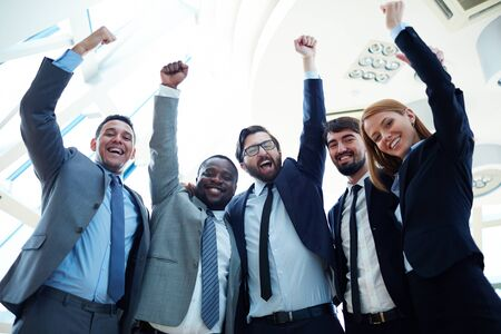 achiever: Ecstatic business partners in suits raising their arms and expressing triumph