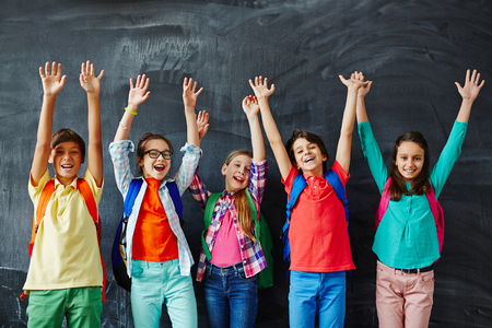 Ecstatic kids raising hands while standing by blackboard Standard-Bild