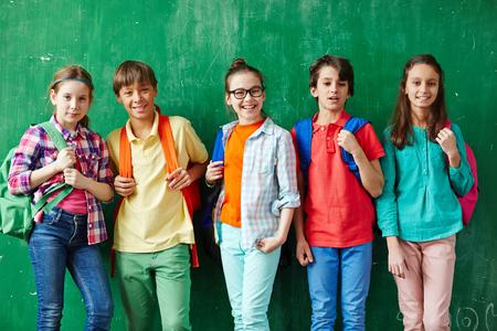 Groep van vriendelijke schoolkinderen met rugzakken kijken naar de camera door bord