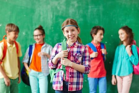 colegiala: La muchacha bonita con mochila mirando a la c�mara con sus compa�eros de clase en el chat en el fondo Foto de archivo