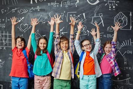 raising: Ecstatic learners raising hands against blackboard