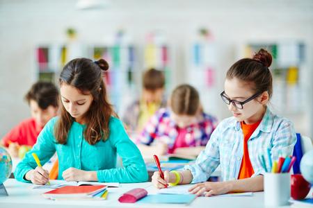 diligente: Pupilas diligentes sentado en el escritorio y que escriben en cuadernos en la lección