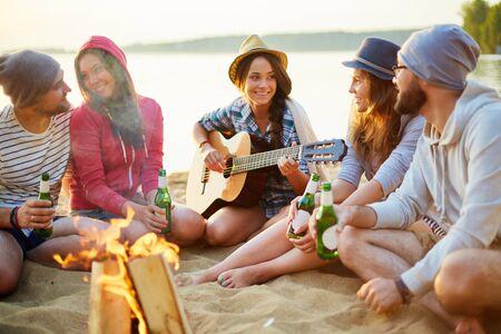 Amigos felices con las bebidas que habla por el fuego de campamento