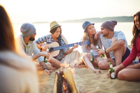 Amigos felices con las bebidas que se sienta en la arena alrededor de la hoguera
