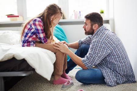 Teenage meisje huilen terwijl haar vader haar geruststellend