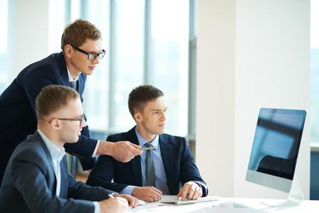 monitor de computadora: Grupo de hombres de negocios confidentes que miran el monitor de la computadora