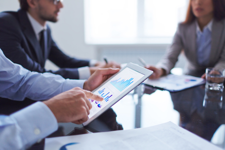 Menselijke hand te wijzen op touchscreen in werkomgeving op vergadering Stockfoto