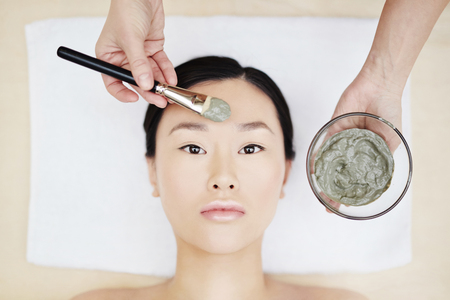 purifying: Young Asian woman having peeling procedure in spa salon Stock Photo