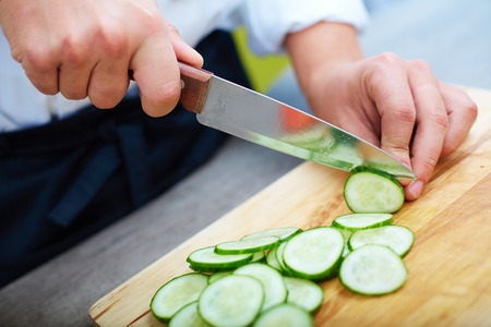 male hand: Close-up of male hands slicing fresh cucumbers Stock Photo