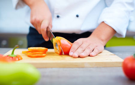 Close-up of cook chopping bell pepper Stock Photo