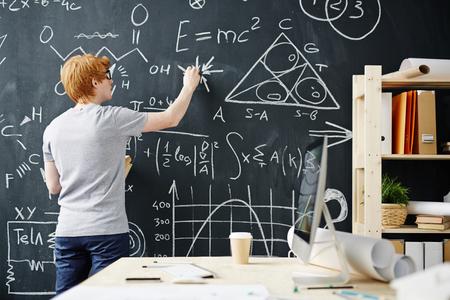 hombre escribiendo: estudiante escribir en la pizarra durante una clase de matemáticas