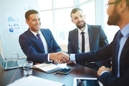 会議中に握手するビジネスマン