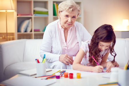 grandkid: Grandmother sitting with her granddaughter while she drawing