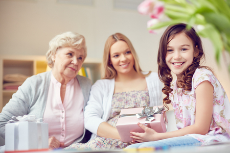 grandkid: Cute girl congratulating her mother and grandmother with Mother's Day Stock Photo