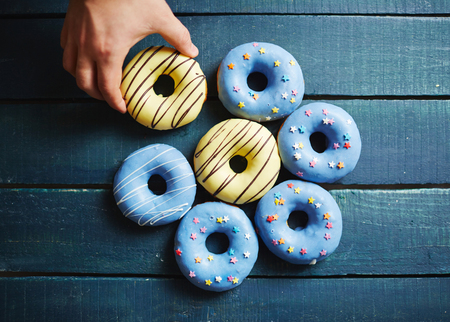 yummy: Close-up of male hand grabbing delicious donut Stock Photo