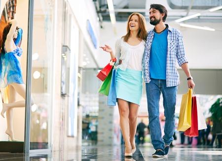 Schöne Paare durch das Einkaufszentrum zu Fuß und mit Einkaufstaschen