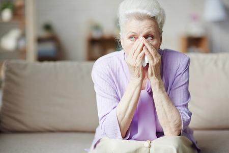 Traurige ältere Frau, die auf Sofa sitzt und weint