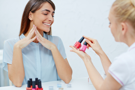 nailcare: Beautician showing nail polishes to enthusiastic female in nailcare salon Stock Photo