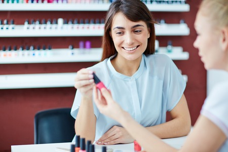 manicurist: Female manicurist showing her client pink nail polish in salon