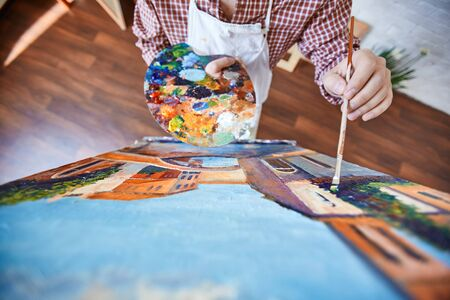 paper art: Artist with brush and palette painting a picture Stock Photo