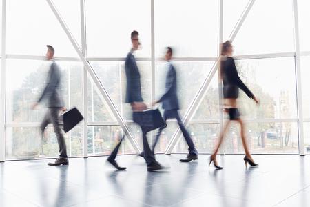 Grupo de gente de negocios a lo largo del pasillo de la oficina durante el día de trabajo