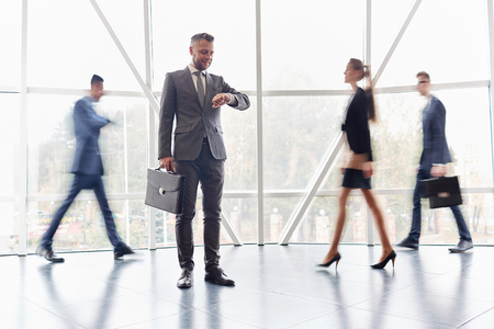 Uomo d'affari con la valigia guardando l'orologio tra gli uomini d'affari che vanno dietro di lui