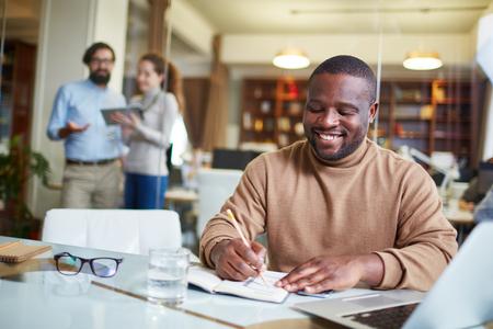 hombre escribiendo: Jóvenes planes de escritura de negocios en su cuaderno de notas con la gente de negocios detrás de él