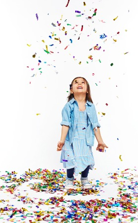 Cute petite fille sous la chute des confettis