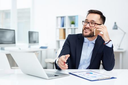 彼の職場で座っているし、電話で話しているアジア系のビジネスマン