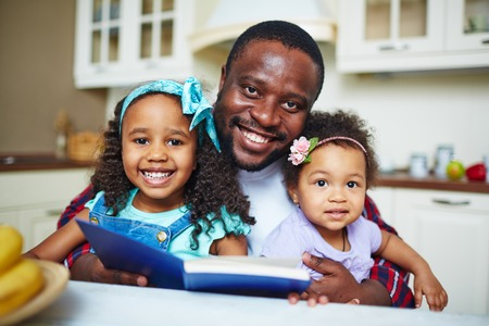 african man: Smiling young father reading a book for his girls