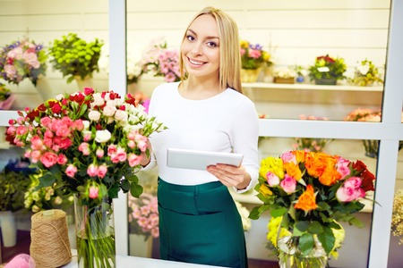 florist shop: Portrait of smiling florist working in flower shop