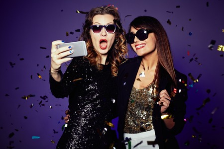 party people: Two beautiful elegant women making selfie Stock Photo