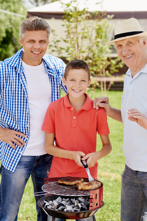 grandkid: Portrait of happy family with barbecue outdoors Stock Photo