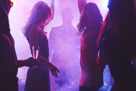 dancing club: Group of dancing people in night club
