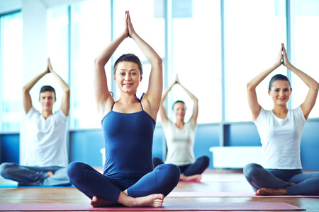 Young woman practicing yoga in yoga class in fitness center