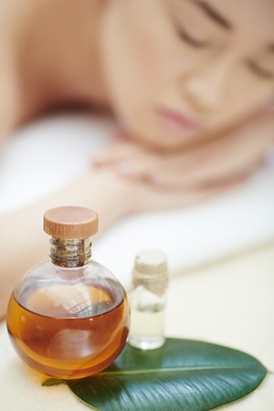cosmetics products: Close-up of spa oil with young woman in the background