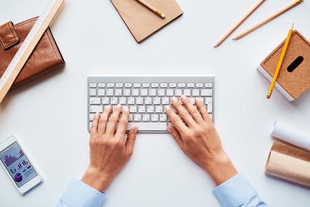 typing: Primer plano de las manos de una hembra que pulsan en la mesa