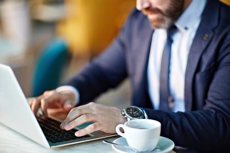 typing: Empresario escribiendo en la computadora portátil y el consumo de café Foto de archivo