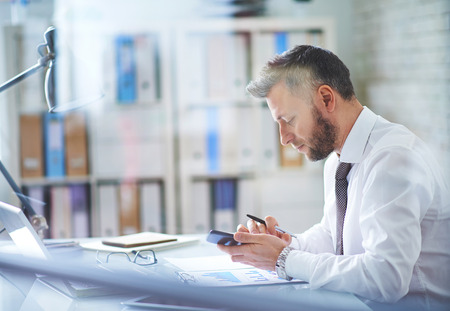 Mature businessman texting in his office photo